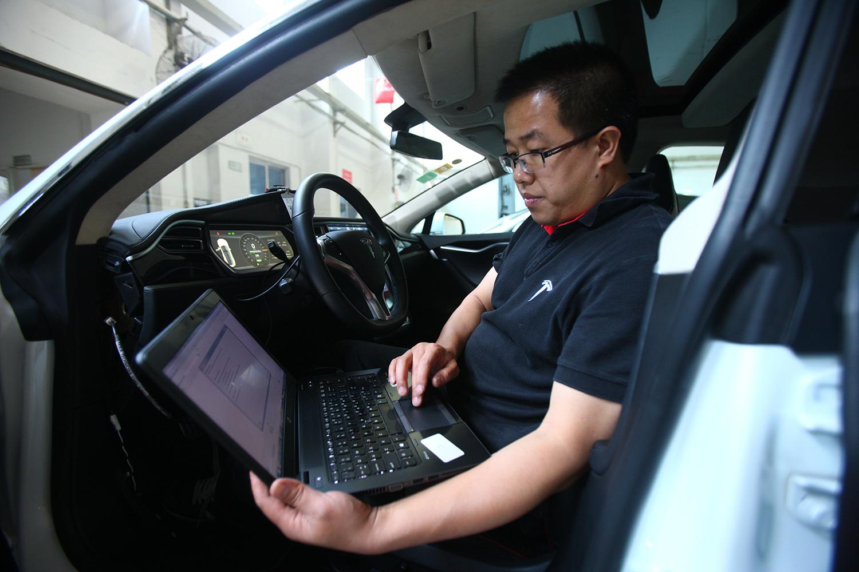 A technician examines a Tesla using a laptop computer.