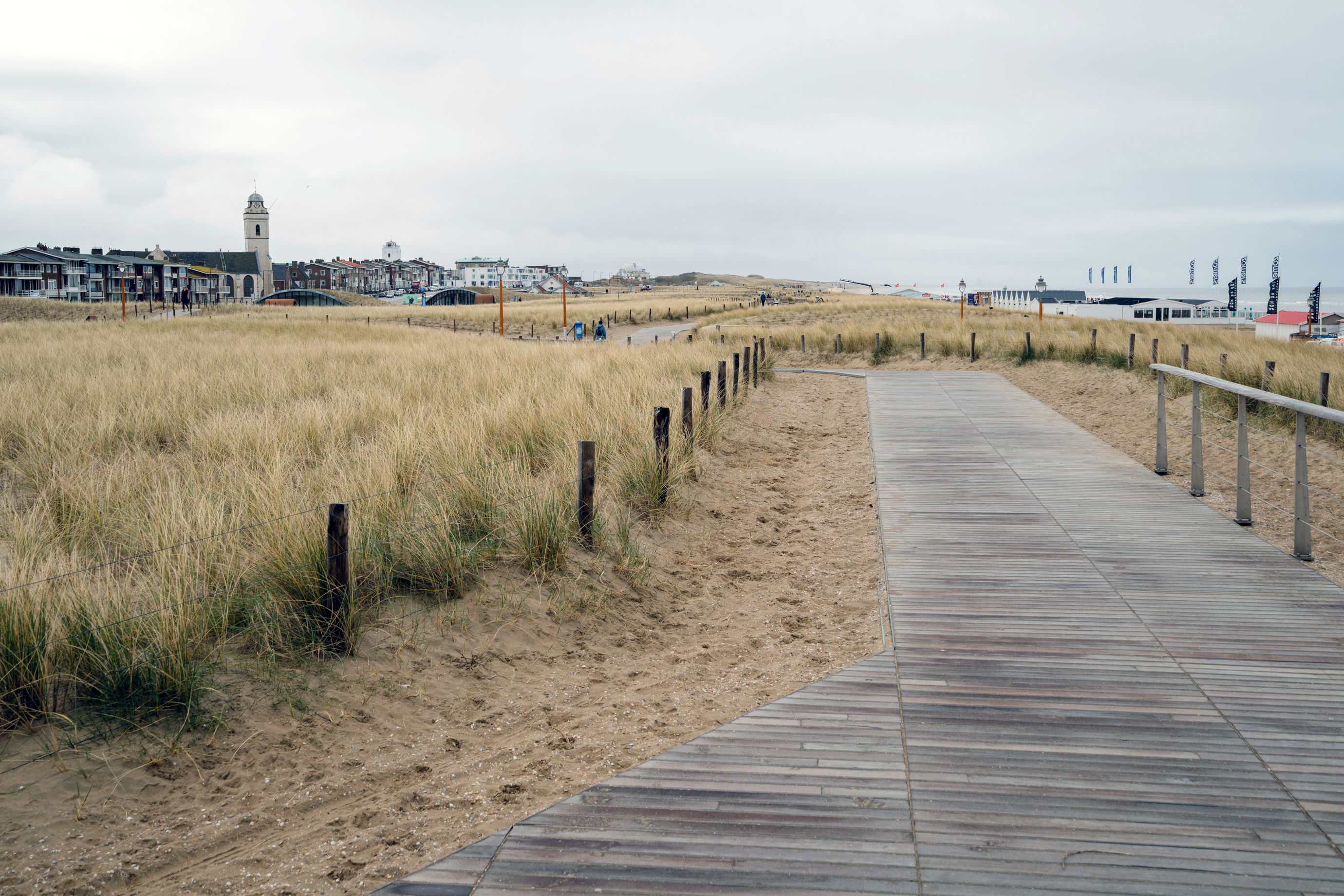 A walkway above the Katwijk multiuse dike, with the ocean to the right. A parking garage is beneath the dunes.
