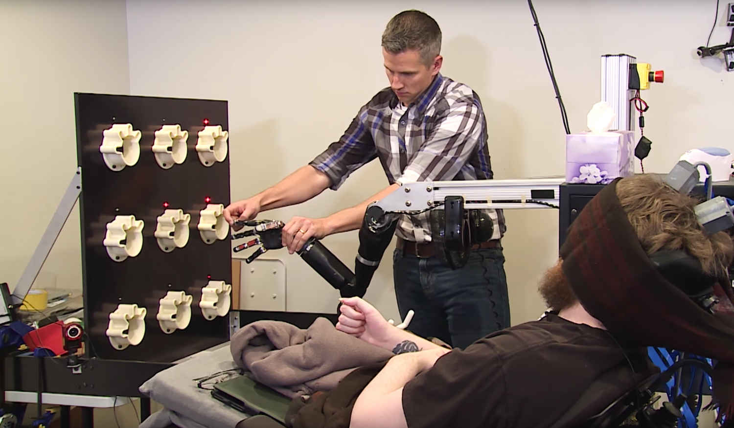 Nathan Copeland, seated, is tested on his sense of touch through a robotic arm.