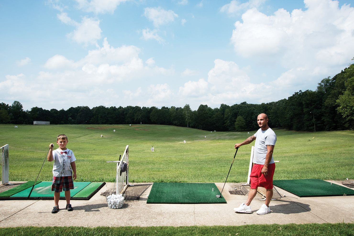 Wes Robida and his son Caden at the driving range on a Sunday afternoon. The family recently relocated from Denver to Greenville, attracted by the strong economy and cost of living. (1 of 10)