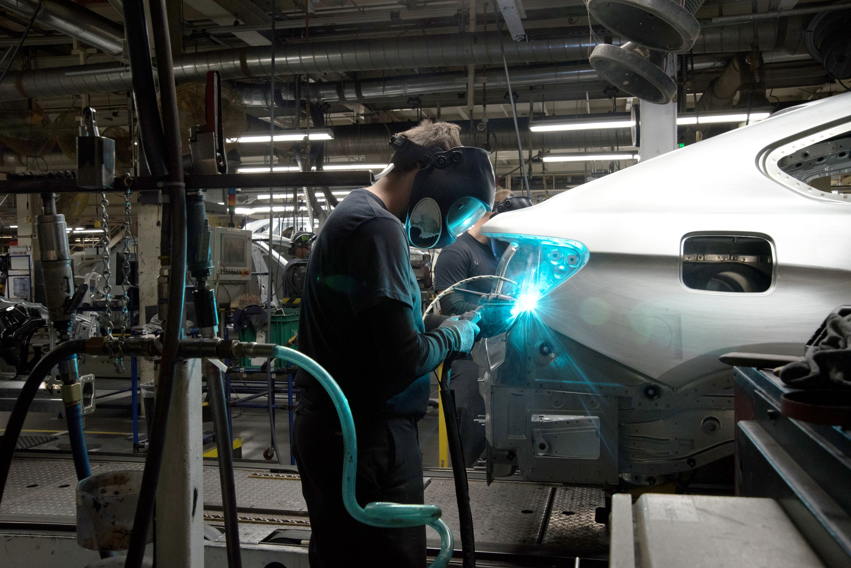 Most of the welding done in the plant's body shop is performed by robots, but certain special welds are still made by workers. (2 of 7)