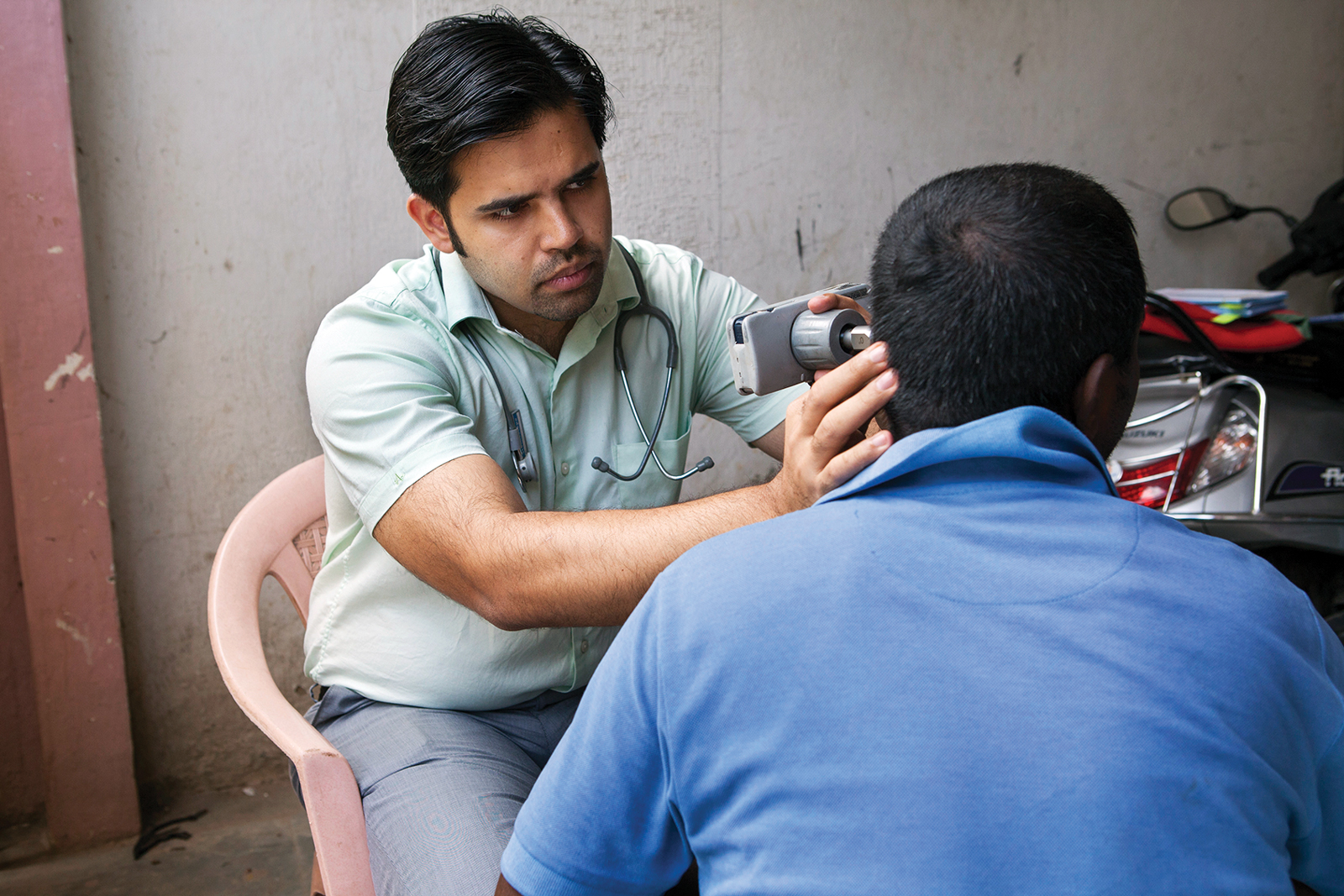 Chaturvedi advises a patient's relatives and uses an early version of the Entraview to examine a man's ear in Bangalore.